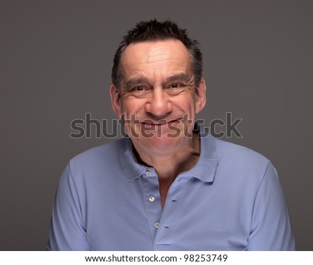 Handsome Middle Age Man Pulling Silly Face Grinning on Grey Background - stock photo