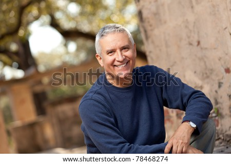 Handsome middle age man with gray hair in an outdoor setting. - stock photo