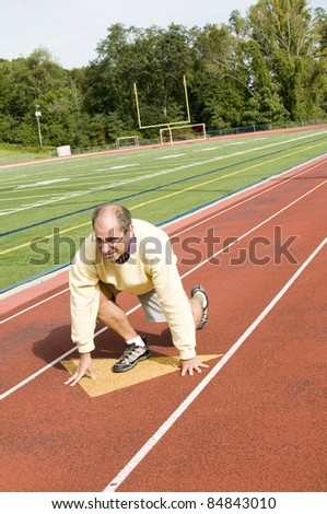 handsome middle age senior man stretching exercising on sports football field and running track - stock photo