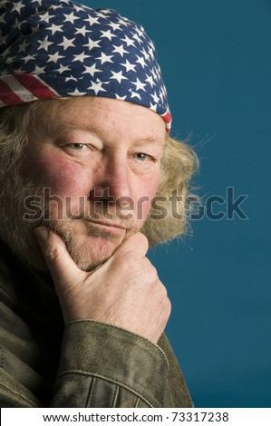 handsome middle age senior man with beard  long hair wearing leather jacket American flag bandana and leather motorcycle jacket - stock photo