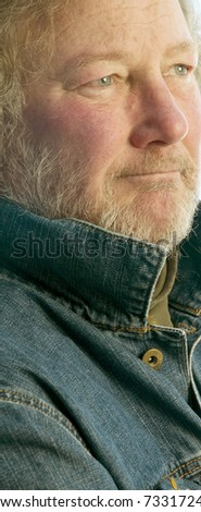 handsome middle age senior man with beard smiling in denim jacket - stock photo