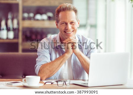 Handsome middle aged businessman in casual clothes is using a laptop and smiling while working at the restaurant - stock photo