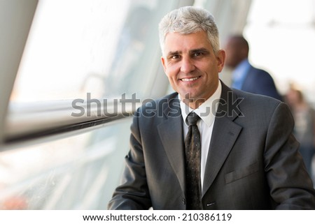 handsome middle aged businessman in modern office - stock photo