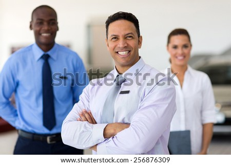 handsome middle aged car salesman with colleagues - stock photo