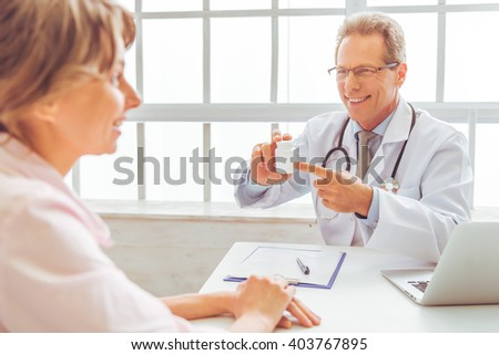 Handsome middle aged doctor is offering medicine to woman on consultation and smiling