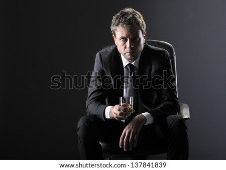 Handsome middle aged man holding a glass of whiskey - stock photo