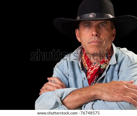 Handsome middle aged man in a cowboy outfit sitting with arms crossed.