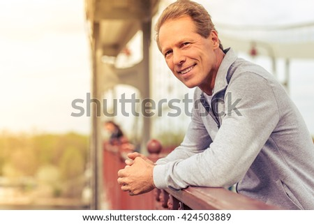 Handsome middle aged man in sports uniform is leaning on bridge, looking at camera and smiling while having break during morning run - stock photo