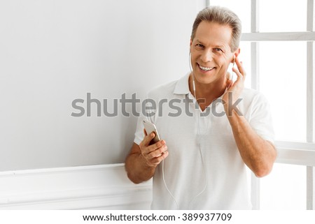 Handsome middle aged man is listening to music using a smart phone and smiling while sitting near the window at home - stock photo