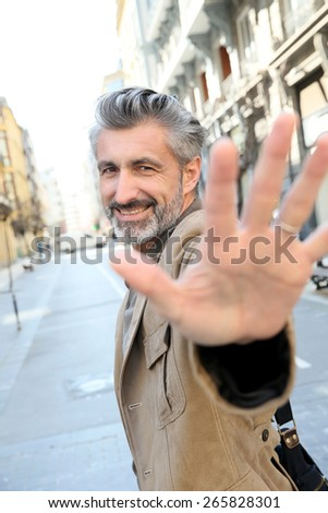 Handsome middle-aged man showing hand to camera - stock photo