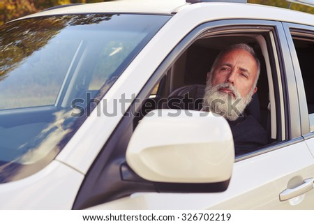 handsome middle-aged man sitting in white the car and looking into the distance