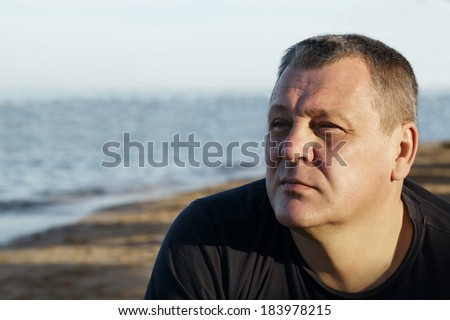 Handsome middle-aged man sitting thinking in the sunlight at the coast with a serious expression and ocean backdrop - stock photo