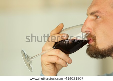 Handsome middle-aged man tasting red wine, close-up - stock photo