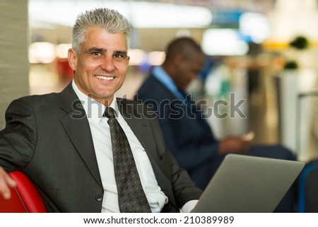 handsome middle aged man waiting at airport lounge - stock photo