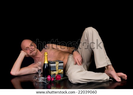 Handsome middle aged man with tattoo with champagne and glasses, studio shot, black background - stock photo