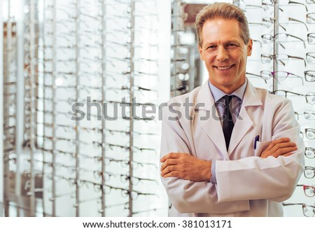 Handsome middle aged ophthalmologist looking at camera and smiling while standing in his office - stock photo