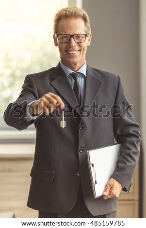 Handsome middle aged realtor in classic suit and eyeglasses is holding a notepad and a key from new apartment, looking at camera and smiling while standing in the room