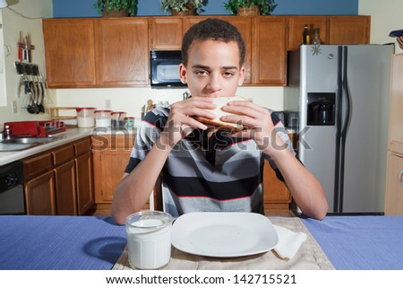 Handsome mixed ethnicity teenaged boy sitting in kitchen ready to eat a peanut butter and jelly sandwich. - stock photo