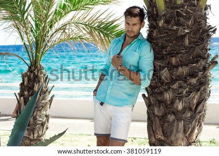 Handsome model in turquoise shirt posing in summer scenery - stock photo