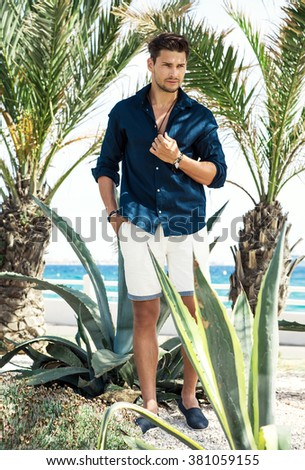 Handsome model posing under the palm tree - stock photo