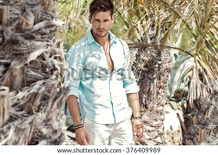 Handsome model under palm tree - stock photo