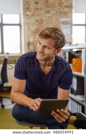 Handsome modern businessman in smart casual clothes sitting in the office in a chair turning and watching something to the side with his tablet in his hands