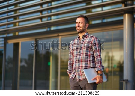 Handsome modern businessman standing outside office - stock photo