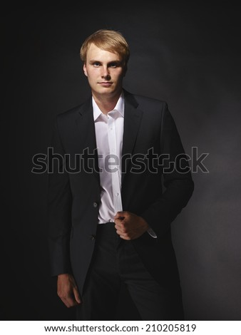 Handsome modern businessman wearing black suit, studio shot dark background
