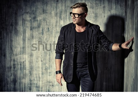 Handsome modern man in black suit and spectacles stands by the wall. Men's beauty, fashion.