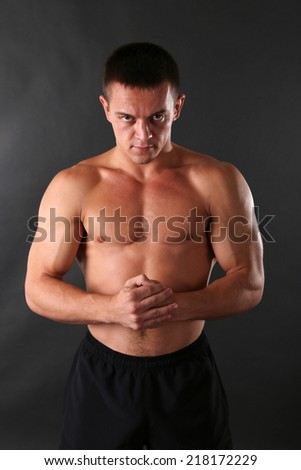 Handsome muscle young man on dark background