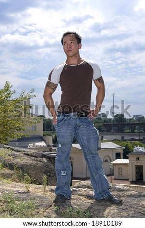 handsome muscular asian man standing on hill - stock photo