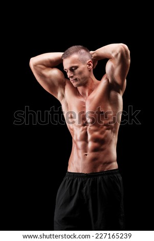 Handsome muscular athlete posing on black background