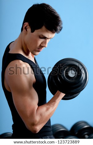 Handsome muscular athletic man uses his dumbbell to exercise flexing bicep muscle - stock photo