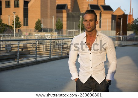 Handsome muscular blond man standing in city setting looking to a side, large copyspace - stock photo