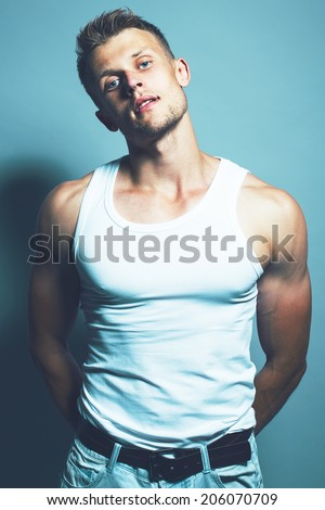 Handsome muscular blonde young man in white undershirt, light jeans and dark brown leather belt with seductive, sexy glass over blue background. Close up. Studio shot. - stock photo