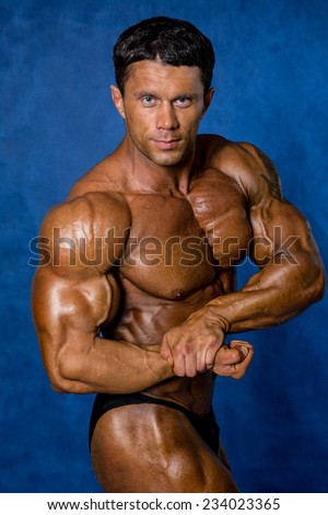Handsome muscular bodybuilder demonstrates his muscles. Beauty of the male body - stock photo
