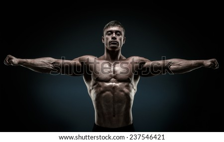 Handsome muscular bodybuilder posing and keeping arms outstretched. Muscular and fit young bodybuilder posing raising his hands on black background. - stock photo