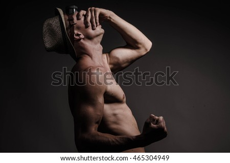 Handsome muscular bodybuilder posing on gray background.