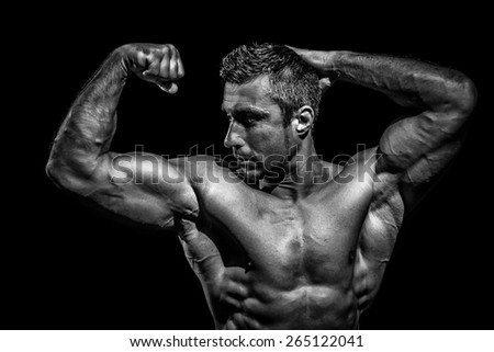 Handsome muscular bodybuilder posing over black background - stock photo