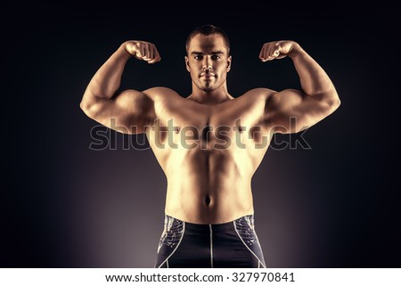Handsome muscular bodybuilder posing over black background. - stock photo