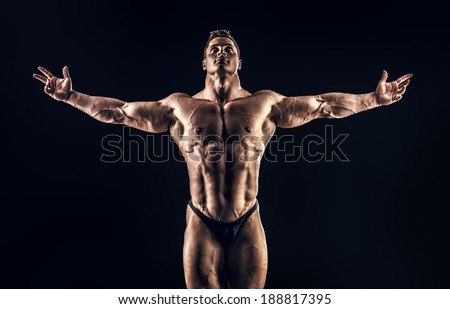 Handsome muscular bodybuilder posing over black background. Glory of the champion. - stock photo