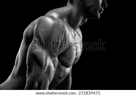Handsome muscular bodybuilder preparing for fitness training, confidently looking forward. Studio shot on black background. Black and white photo.