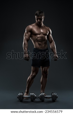 Handsome muscular bodybuilder preparing for fitness training. Pumping up muscles with dumbbells. Studio shot on black background. - stock photo