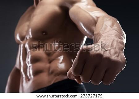 Handsome muscular bodybuilder shows his fist and vein, blood vessels. Studio shot on dark background. - stock photo