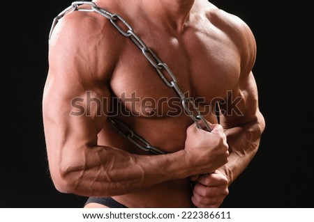 Handsome muscular bodybuilder with chain posing over black background - stock photo