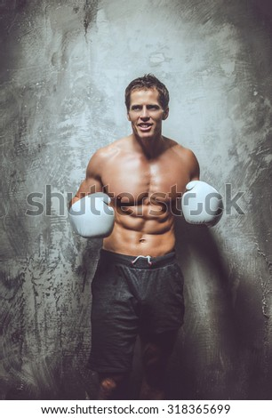 Handsome muscular boxer posing over grey wall.