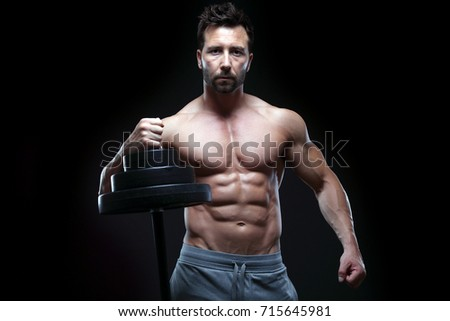 Handsome muscular guy relaxing after training, isolated on black background