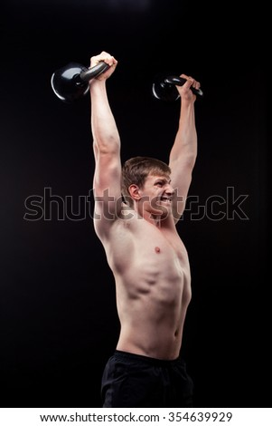 Handsome muscular guy with kettlebells isolated on black background.