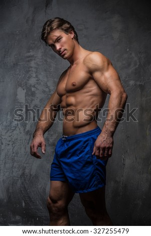 Handsome muscular male in blue shorts. Isolated on grey background.