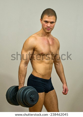 Handsome muscular male model with dumbbell. - stock photo